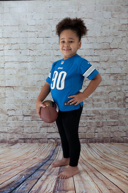 Young girl holding a football wearing a Detroit Lions football jersey