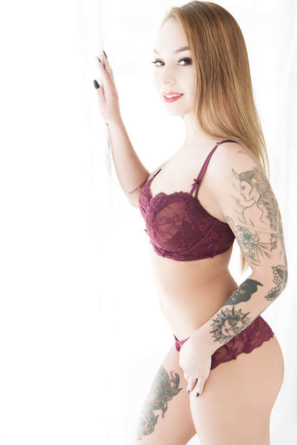 Beautiful young woman with tattoos posing in a bra and panties in a window light boudoir photo shoot