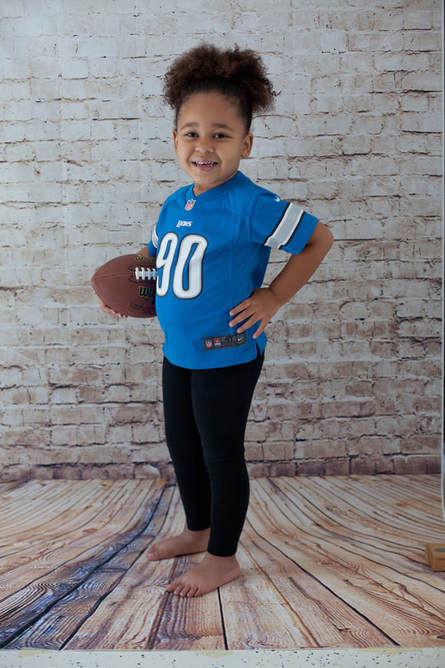 Girl holding a football wearing a Detroit Lions jersey