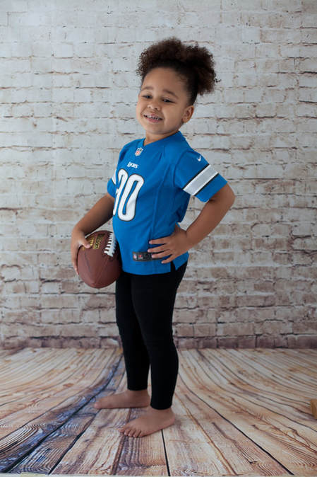 Young girl holding a football wearing a Detroit Lions jersey