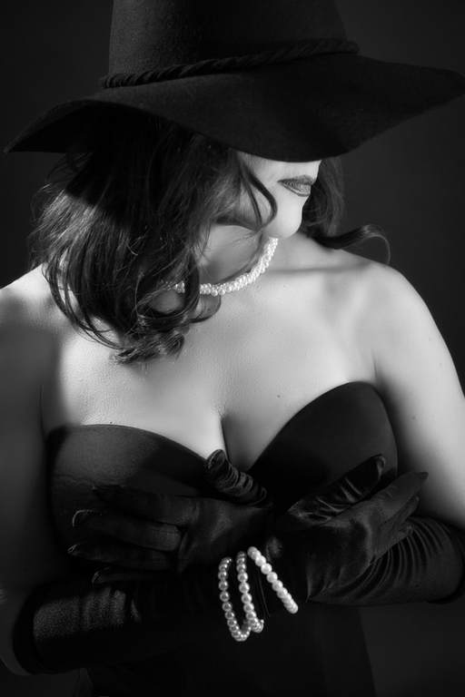 Woman wearing a black hat covering her eyes in a vintage glamour photo