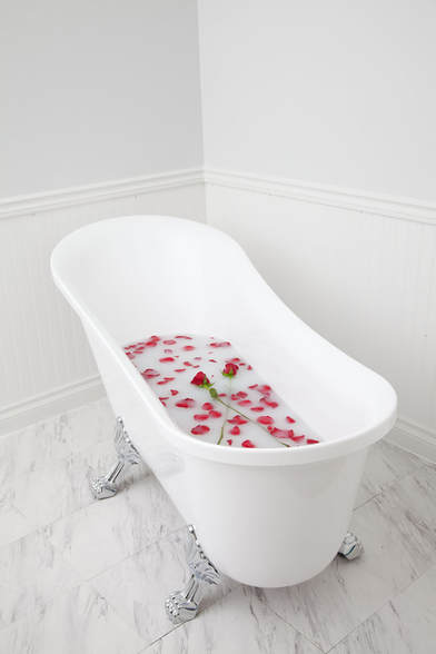 A romantic claw foot bathtub filled with milk bath and rose petals