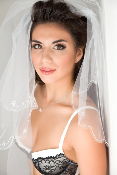 Beautiful young bride wearing a veil in a bridal boudoir photo shoot