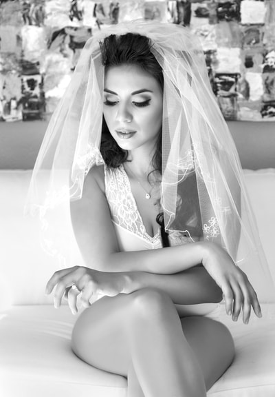 Beautiful young bride wearing lingerie and a veil posing for a bridal boudoir photo shoot