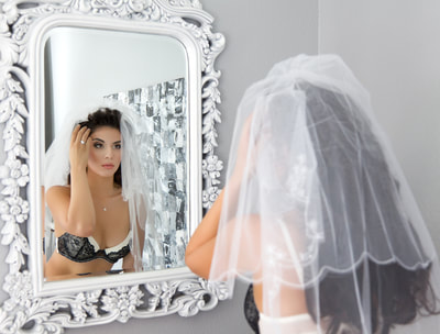A bridal boudoir photo shoot of a woman wearing a bra and bridal veil