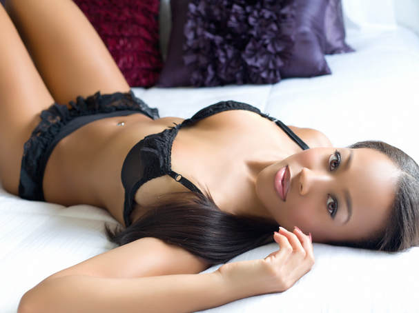 Boudoir photography pose of a fitness model in her underwear laying on a bed