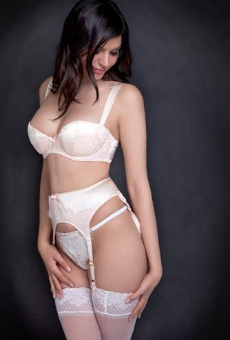Beautiful boudoir photo of a woman wearing a white garter belt bra and panties
