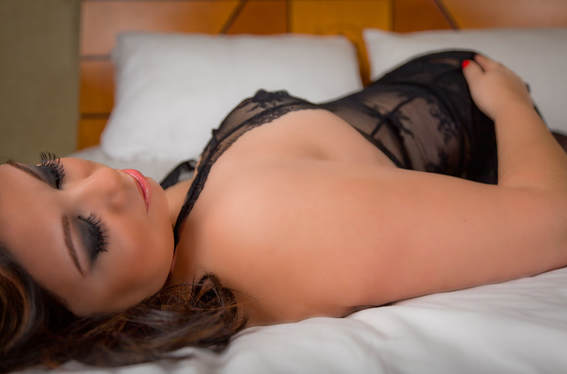 Curvy boudoir photo of a woman wearing lingerie laying on a bed