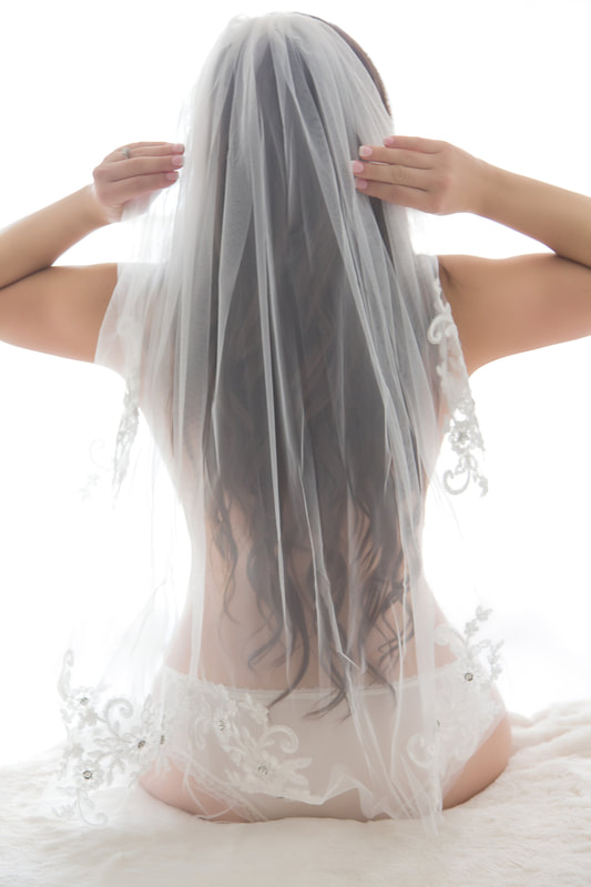 Bridal boudoir photo of a bride-to-be in her panties putting on her veil