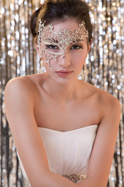 Glamour photo shoot of a young woman wearing a masquerade mask