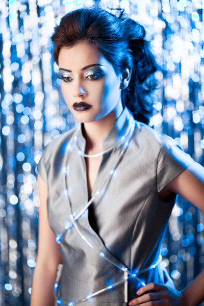 A fashion photo of a young female model posing with LED lights wrapped around her
