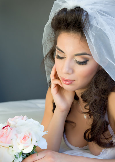 Beautiful bridal boudoir portrait of a young bride looking at her bouquet of flowers