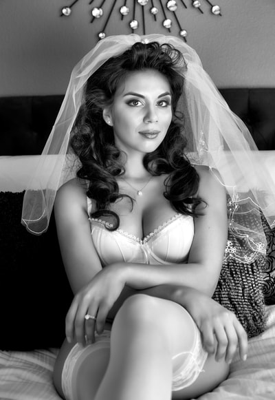 black and white portrait of a young woman wearing a white bra and panties and a wedding veil sitting on a bed in a bridal boudoir pose