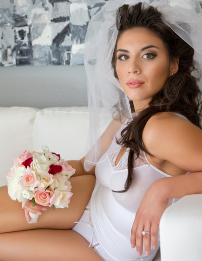 young woman holding a bridal bouquet posing on a white couch during a bridal boudoir photo shoot