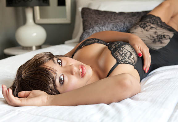 Las Vegas Boudoir Photography photo of a sexy young female model wearing black lingerie laying on her back in a bed looking while looking at the camera