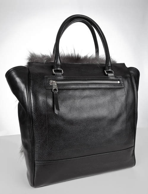 Back side featuring black leather and a zipper of the Coach Legacy Tanner Tote