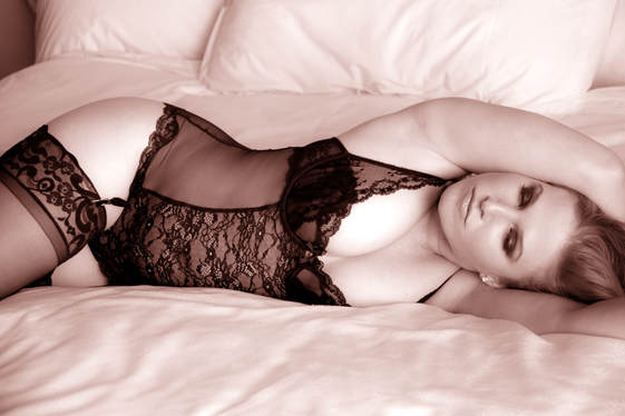 Boudoir photography of a beautiful woman in lingerie wearing a black bustier and black thigh high stockings, laying across a bed showing her sexy curvy figure