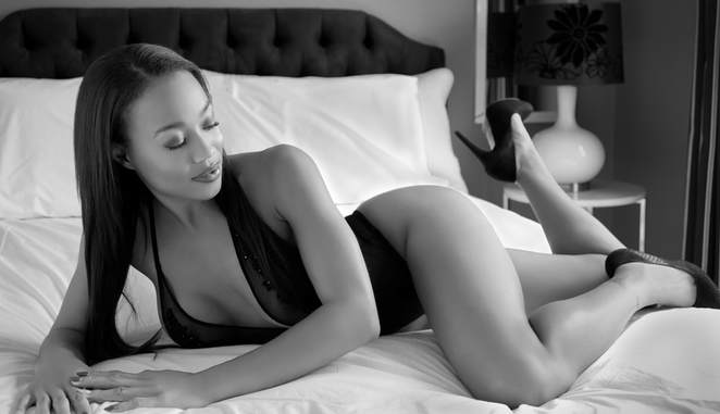 Sexy boudoir photo of a fitness model posing on a bed