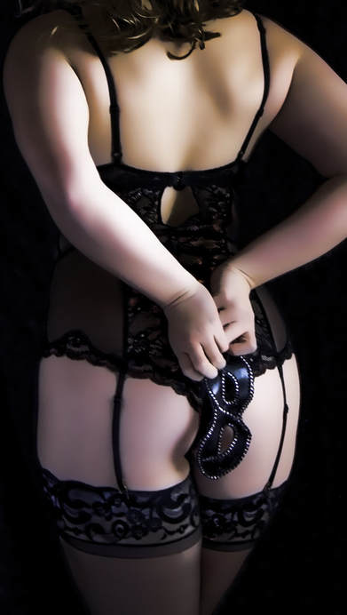 Curvy girl boudoir photography of a female in lingerie and black thigh high stockings, holding a masquerade mask over her round sexy ass
