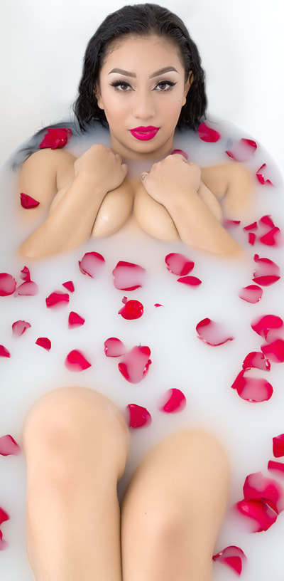 Valentines day milk bath boudoir photo shoot by Las Vegas Glamour Boudoir of a woman surrounded by rose petals