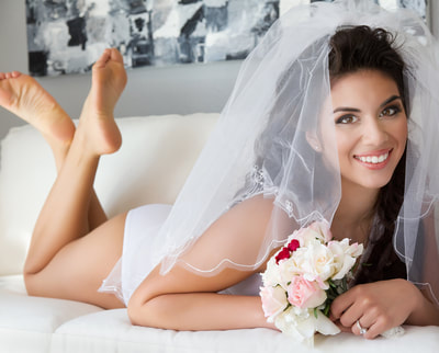 Sexy young woman wearing a bridal veil and white lingerie laying on a sofa during a bridal boudoir photo shoot