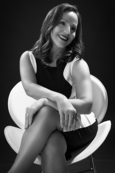 Woman sitting in a white leather chair in a vintage glamour photography photo